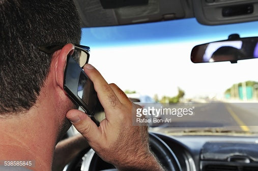 male-driver-speaking-on-mobile-phone-while-driving-picture-id538585845.jpg